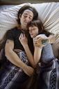 Man and woman sleeping on bed in camper van - CAVF23726