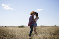 Side view of couple kissing on field against sky - CAVF23744