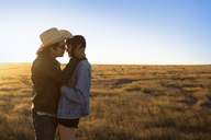 Couple standing on field against clear sky during sunset - CAVF23756