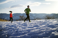 Couple jogging on snow field against sky - CAVF23852