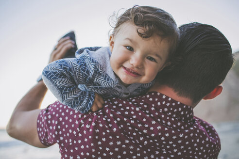 Portrait of smiling baby boy being carried by father at beach - CAVF23888