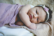 Close-up portrait newborn baby girl lying on bed - CAVF23903