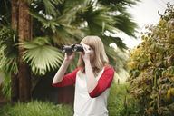 Teenager looking through binoculars while standing by plants at park - CAVF23936