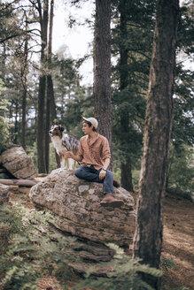 Man with Australian Shepherd in forest - CAVF23960