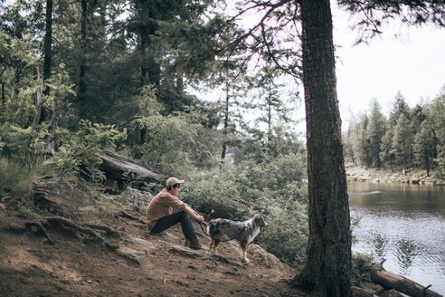 Side view of man with Australian Shepherd by lake in forest - CAVF23966