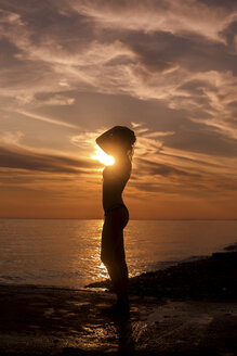 Side view of silhouette sensuous woman standing on beach during sunset - CAVF24032