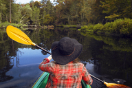 Rear view of woman kayaking in lake at forest - CAVF24065