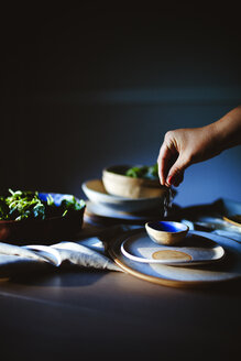 Cropped hand of woman sprinkling salt in bowl while preparing salad at home - CAVF24200