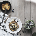 Overhead view of pancake in plate on wooden table - CAVF24203