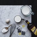 Overhead view of milk and alcohol with egg on table against black background - CAVF24206