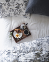 Overhead shot of breakfast tray loaded with croissant, fried egg and coffee on bed - CAVF24329