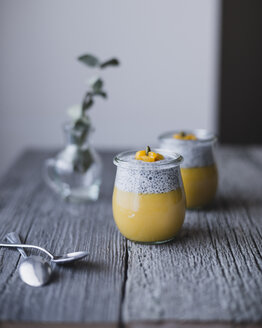 Jars of chia with mango pudding on wooden table - CAVF24347