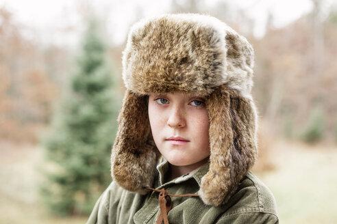 Portrait of boy in warm clothing standing on field - CAVF24389