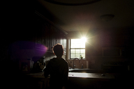 Silhouette boy looking bright sun through window while standing in kitchen - CAVF24422