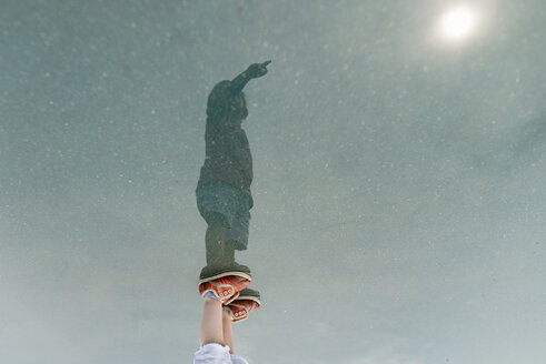 Reflection of boy with hand raised standing in puddle - CAVF24440