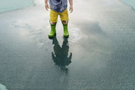Low section of boy in rubber boots standing in puddle - CAVF24449