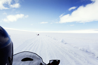 Cropped image of person riding snowmobile on landscape against sky - CAVF24538