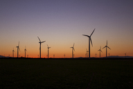Silhouette wind turbines on field against clear sky during sunset - CAVF24541
