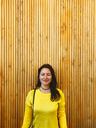 Portrait of woman standing against wooden wall - CAVF24553
