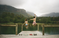 Rear view of excited friends jumping from jetty in lake against mountains - CAVF24601
