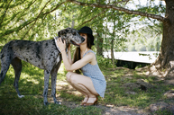 Full length of woman kissing Great Dane at park - CAVF24610