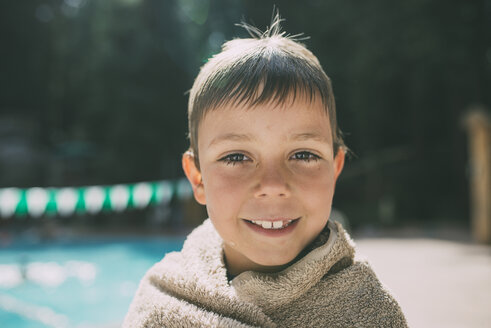 Portrait of happy boy wrapped in a towel standing at poolside - CAVF24654