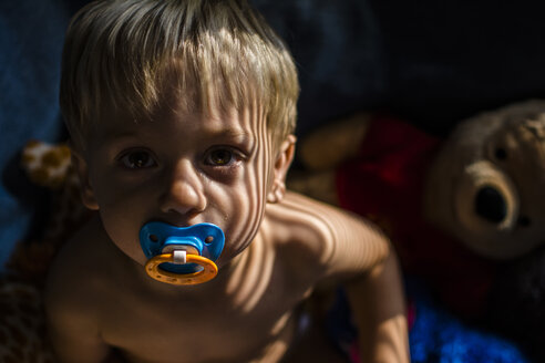 Portrait of shirtless boy with pacifier in mouth at home - CAVF24726
