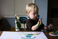 Cute boy drawing on paper while sitting at home - CAVF24729