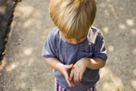 High angle view of boy looking at caterpillar on hand - CAVF24735