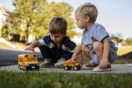 Brothers playing with toys in backyard - CAVF24738