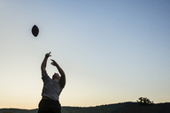 Low angle view of man playing football against clear sky during sunset - CAVF24750