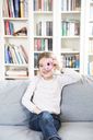 Portrait of laughing little girl with doughnut sitting on couch - LVF06820