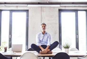Mature businessman sitting barefoot on desk in office meditating - HAPF02652