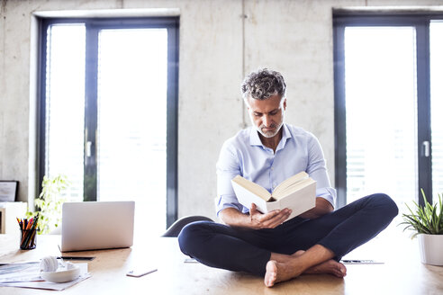 Mature businessman sitting barefoot on desk in office reading a book - HAPF02655