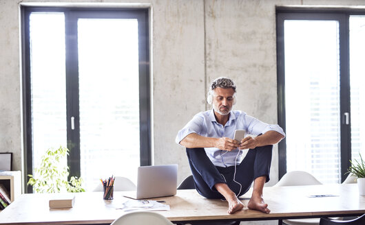 Mature businessman with smartphone and headphones sitting barefoot on desk in office - HAPF02658