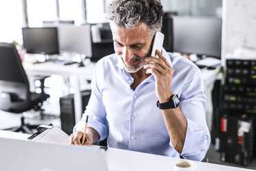Smiling mature businessman sitting at desk in office talking on smartphone - HAPF02670