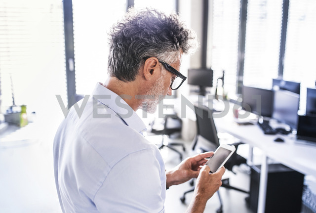 Mature businessman in office using smartphone - HAPF02688 - HalfPoint/Westend61