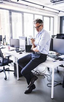 Mature businessman sitting on desk in office using smartphone - HAPF02691