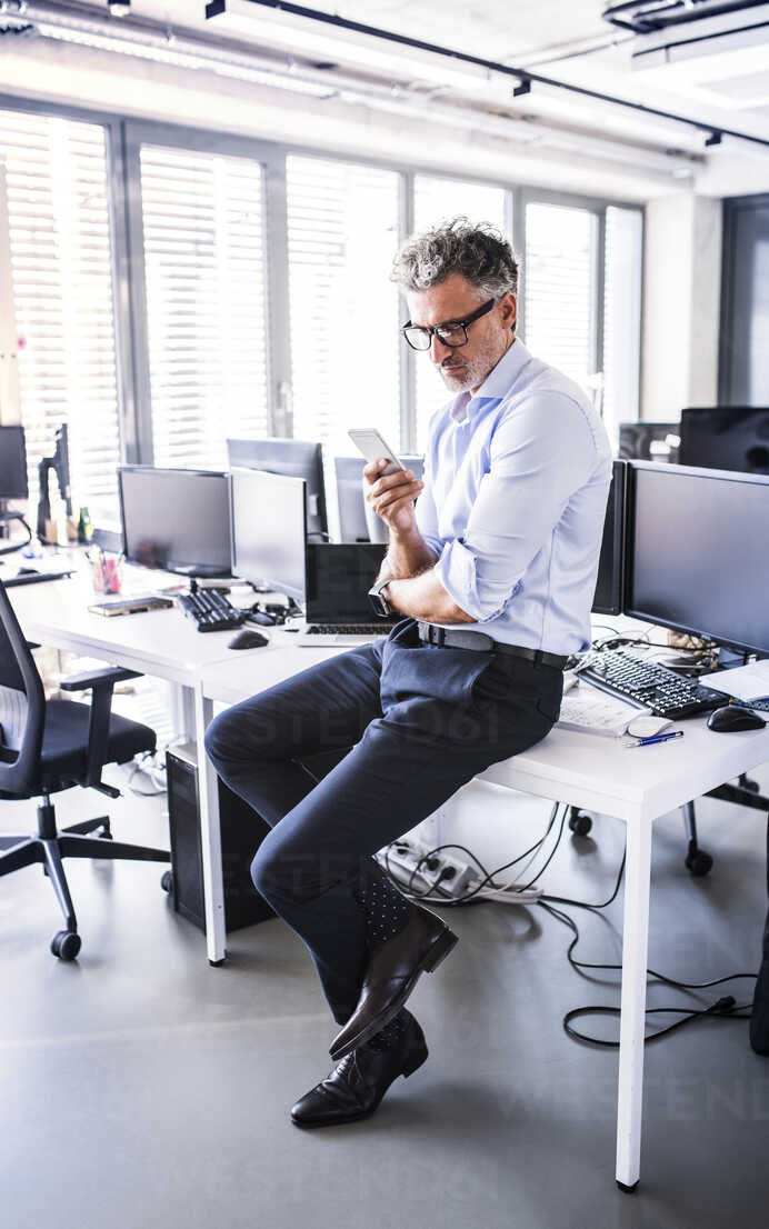 Mature businessman sitting on desk in office using smartphone - HAPF02691 - HalfPoint/Westend61