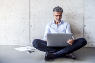 Mature businessman sitting on the floor using laptop - HAPF02694