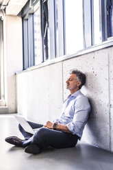 Mature businessman with laptop sitting on the floor leaning against the wall - HAPF02697