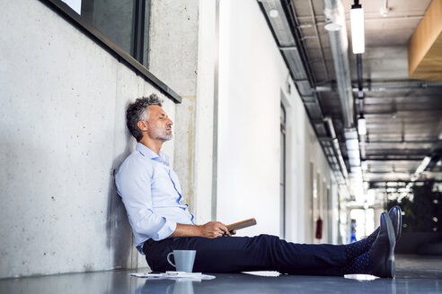 Mature businessman sitting on the floor leaning against the wall - HAPF02700