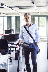 Portrait of smiling mature businessman with scooter in office - HAPF02703