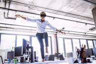 Barefoot mature businessman on desk in office wearing VR glasses - HAPF02709
