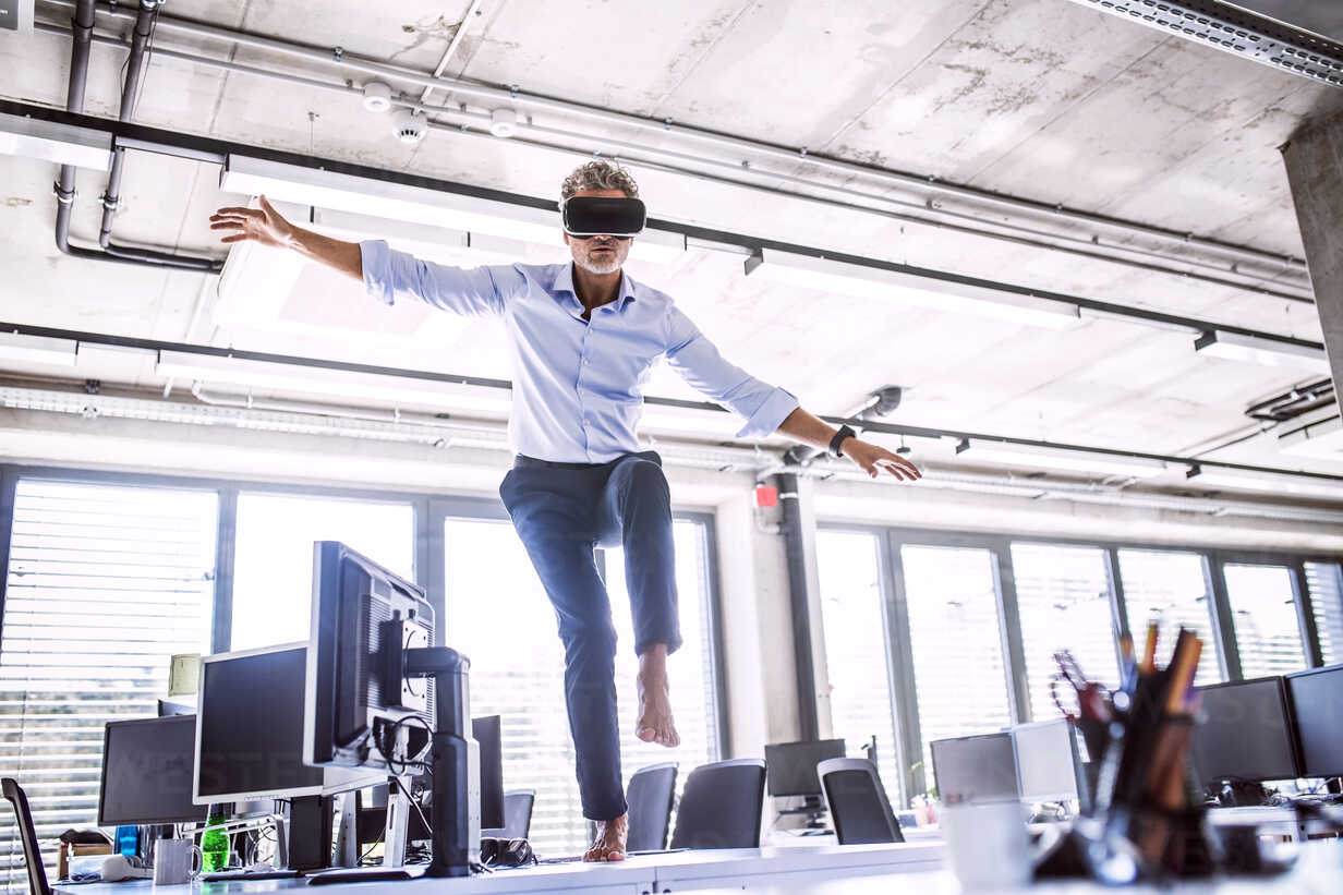 Barefoot mature businessman on desk in office wearing VR glasses - HAPF02709 - HalfPoint/Westend61