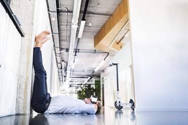 Barefoot mature businessman lying on floor in office wearing VR glasses - HAPF02712