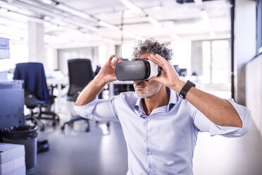 Mature businessman wearing VR glasses in office - HAPF02715