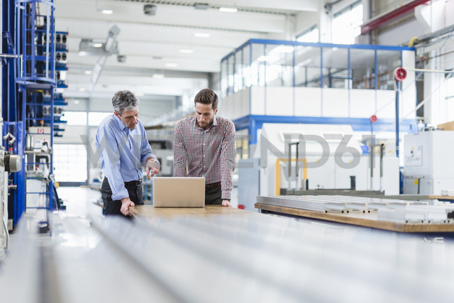 Businessmen using laptop in production hall - DIGF03484