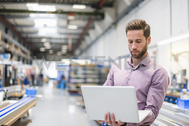 Young businessman using laptop in production hall - DIGF03493