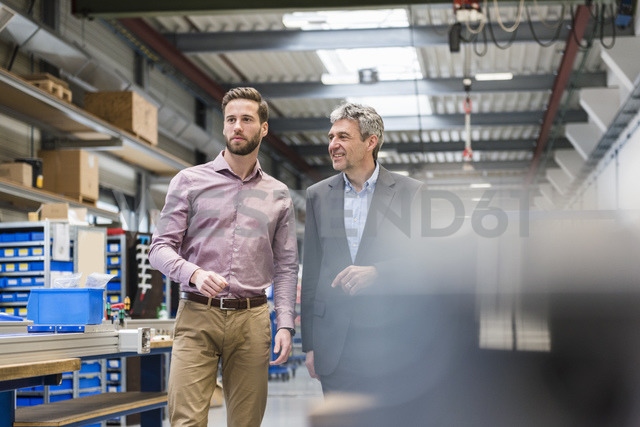 Businessmen during meeting in production hall - DIGF03496